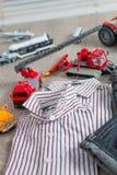 Обмундирование мальчика близко установленное игрушки автомобиля Striped рубашка, джинсовая ткань задыхается желтые и красные авто Стоковые Фото