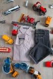 Обмундирование мальчика около игрушки автомобиля Striped рубашка, брюки джинсовой ткани и голубая шлюпка обувают желтые красные а Стоковое Изображение