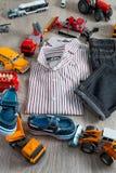 Обмундирование мальчика около игрушки автомобиля Striped рубашка, брюки джинсовой ткани и голубая шлюпка обувают желтые красные а Стоковые Фото