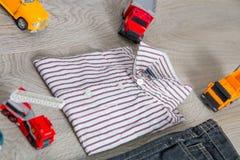 Обмундирование мальчика около игрушки автомобиля Striped рубашка, джинсовая ткань задыхается желтые и красные автомобили конец вв Стоковые Изображения