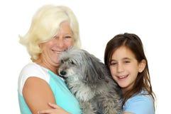 обнимать бабушки девушки семьи собаки Стоковое Фото