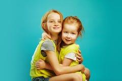 Обнимать красной с волосами сестры ребенка 2 милый изолированный на голубой предпосылке стоковое изображение