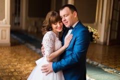 Обнимать очаровательного жениха и невеста симпатичный в роскошном интерьере стоковое фото rf
