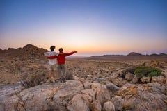 Обнимать пар при протягиванные оружия наблюдая сногсшибательный взгляд пустыни Namib, величественная привлекательность посетителя Стоковое Изображение