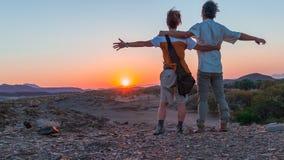 Обнимать пар при протягиванные оружия наблюдая сногсшибательный взгляд пустыни Namib, величественная привлекательность посетителя Стоковое фото RF
