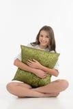 Обнимать подушку. Жизнерадостный девочка-подросток обнимая подушку и уборную Стоковое Фото