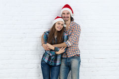 Обнимать улыбки влюбленности крышки, человека и женщины шляпы Санты Нового Года носки пар праздника рождества счастливый стоковое изображение rf