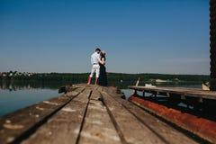 Обнимать человека и женщины в влюбленности на деревянной пристани Стоковое Изображение RF