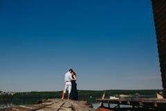 Обнимать человека и женщины в влюбленности на деревянной пристани Стоковые Изображения RF