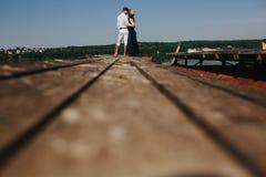 Обнимать человека и женщины в влюбленности на деревянной пристани Стоковое фото RF