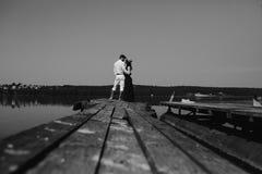 Обнимать человека и женщины в влюбленности на деревянной пристани Стоковая Фотография