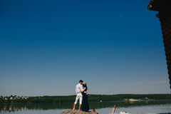 Обнимать человека и женщины в влюбленности на деревянной пристани Стоковое Изображение