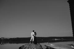 Обнимать человека и женщины в влюбленности на деревянной пристани Стоковое Фото