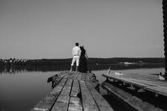 Обнимать человека и женщины в влюбленности на деревянной пристани Стоковые Фото
