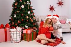 Обнимать человека и женщины сидя около рождественской елки Стоковые Изображения RF