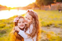 2 обнимая девушки на побережье реки Стоковые Изображения