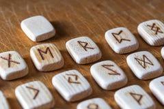 Обозначены англосаксонские деревянные handmade runes на винтажной таблице на каждом символе rune для говорить удачи стоковое фото rf