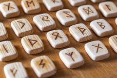 Обозначены англосаксонские деревянные handmade runes на винтажной таблице на каждом символе rune для говорить удачи стоковая фотография rf