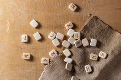 Обозначены англосаксонские деревянные handmade runes на винтажной таблице на каждом символе rune для говорить удачи стоковое изображение rf
