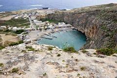 Обозревая внутреннее море с маленькими домами рядом с ним и голубым океаном на заднем плане в gozo, Мальте стоковая фотография rf