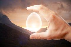 Обои яйца удерживания руки стоковая фотография