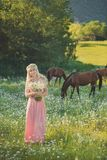Обольстительная белокурая женщина дамы голубых глазов в pinky воздушном платье на луге стоцвета маргаритки держа букет nflowers в Стоковое Изображение