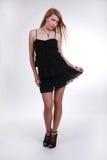 обольстительная девушка в коротком черном платье Стоковое Фото