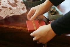 Оборачивать красный подарок с лентой на деревянном столе стоковое изображение rf