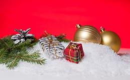 Оборачивать подарка, рему рождественской елки и желтый шарик рождественской елки на снеге Стоковые Изображения