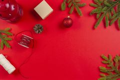 Оборачивать подарка рождества Ветви ели, конусы сосны и присутствующие подарочные коробки на красной предпосылке стоковое изображение rf