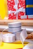 Оборачивать подарка, коробки, бумага, лента и ножницы на предпосылке цвета Аксессуары материалов для настоящих моментов конец вве Стоковая Фотография RF