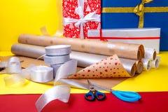 Оборачивать подарка, коробки, бумага, лента и ножницы на предпосылке цвета Аксессуары материалов для настоящих моментов конец вве Стоковое фото RF