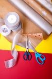 Оборачивать подарка, коробки, бумага, лента и ножницы на предпосылке цвета Аксессуары материалов для настоящих моментов Взгляд св Стоковое Фото