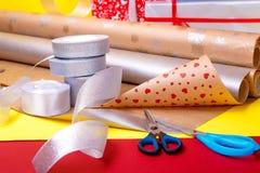 Оборачивать подарка, коробки, бумага, лента и ножницы на предпосылке цвета Аксессуары материалов для настоящих моментов конец вве Стоковые Фотографии RF