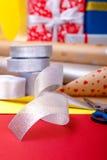 Оборачивать подарка, коробки, бумага, лента и ножницы на предпосылке цвета Аксессуары материалов для настоящих моментов конец вве Стоковое Изображение RF