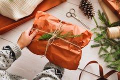 Оборачивать подарок подарка на рождество на белой деревянной предпосылке Стоковое Изображение