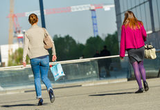 Оборона Ла, Франция 10-ое апреля 2014: задний взгляд 2 вскользь работников идя на улицу Одно носит насосы и другое черное baller Стоковые Изображения