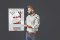 Оборона тезиса Молодой бородатый бизнесмен, одетый в белом плакате рубашки, положения и удерживания с диаграммами Стоковая Фотография