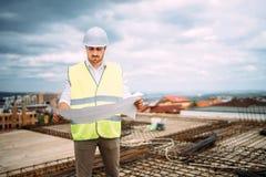 Оборудование для обеспечения безопасности мужского инженера нося на строительной площадке пока наблюдающ строительства Чтение bl  стоковые изображения rf