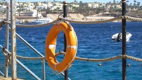 Оборудование для обеспечения безопасности, томбуй жизни или томбуй спасения на деревянной пристани на пляже акции видеоматериалы