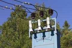 Оборудование для передачи электричества и трансформатор высокого напряжения против голубого неба и зеленых деревьев Стоковые Изображения