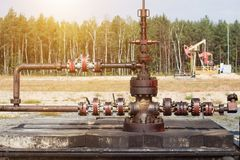 Оборудование для продукции нефти и газ, на заднем плане колодец который масло насосов, продукция, экземпляр-космос стоковая фотография