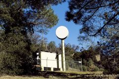 Оборудование связи заключенное в загородку между деревьями стоковые изображения
