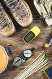 Оборудование с ботинками, компас пешего туризма или перемещения, бинокли, спички на деревянной предпосылке Активная принципиальна Стоковые Фотографии RF