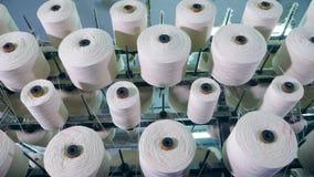 Оборудование фабрики ткани Катушкы вращают с белыми потоками разматывая акции видеоматериалы