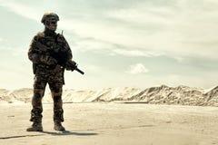 Оборудованный солдат армии с прогулками винтовки в пустыне стоковая фотография