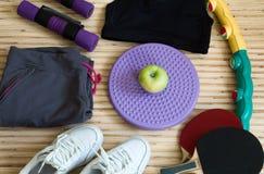 Оборудование фитнеса и концепция здорового образа жизни, тапок, обруча, тенниса, гантелей, тетрадь Яблока, Стоковые Фото