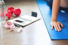 Оборудования спорта и здоровые аксессуары образа жизни при женщина делая йогу Стоковые Фото