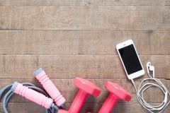 Оборудования спорта и фитнеса с чернью и наушники на древесине Стоковое Изображение
