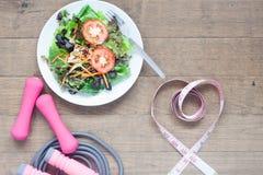 Оборудования спорта, свежий салат и измерять-лента в сердце формируют Стоковые Фото